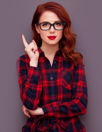 Roodharige meisje in glazen op een grijze achtergrond