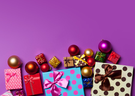 Christmas baubles and gifts on violet background Foto de archivo