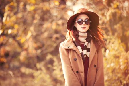 girl alone: Woman in coat with hat and scarf in autumn park
