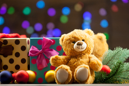 christmas  eve: Teddy bear and christmas gifts with fairy lights on background Stock Photo