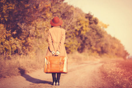 mujer con maleta: woman with bag at countryside in autumn time Foto de archivo
