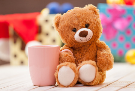 cute teddy bear: Teddy bear with cup of coffee or tea on christmas background