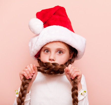 Beautiful little girl with pigtails in Santa Claus hat on pink background
