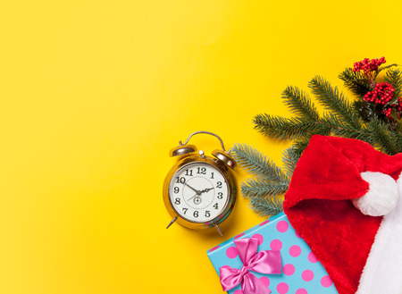Alarm clock and Christmas gifts on yellow background Stock Photo