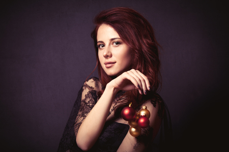 girl in red dress: Portrait of a beautiful woman in style dress with christmas baubles on dark backgorund Stock Photo