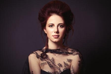 Portrait of a beautiful woman in style dress on dark backgorund