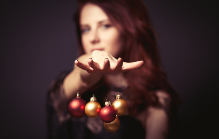 woman shadow: Portrait of a beautiful woman in style dress with christmas baubles on dark backgorund Stock Photo
