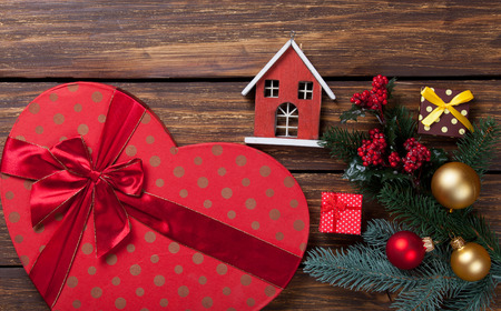 toy house: Heart shape box and toy house on wooden background Stock Photo