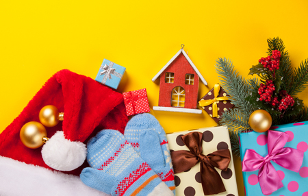 christmas house: Christmas gifts and house toy on yellow background