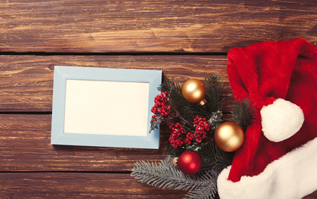 christmas decor: Photo frame and christmas gifts on wooden background