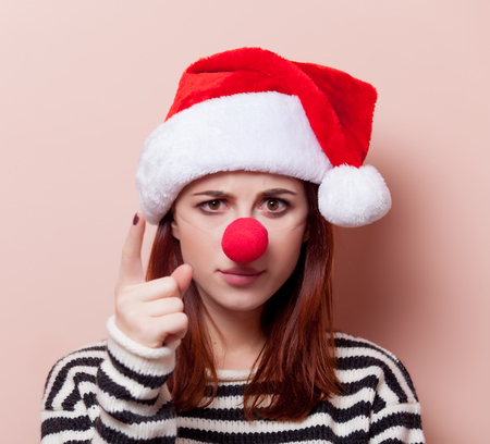 clown nose: Portrait of a young redhead woman in Santa Claus hat with red clown nose on pink background Stock Photo