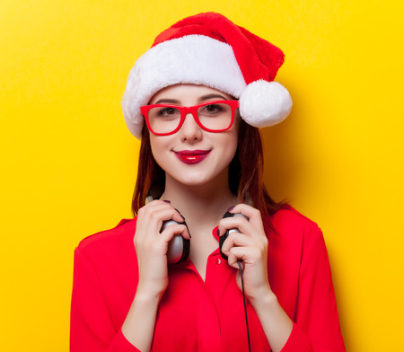 yellow background: Portrait of a young redhead woman in Santa Claus hat and headphones on yellow background