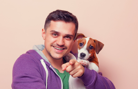 jack russell terrier puppy: Portrait of a young man with jack russell terrier puppy on pink background