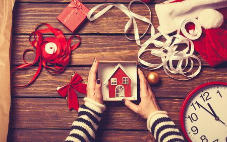 女性の手が木製の背景にクリスマス プレゼントをラッピングします。