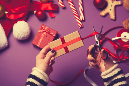 fun background: Female hands are wrapping a christmas gift on violet background Stock Photo