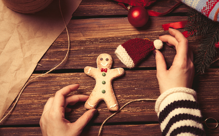 christmas toys: Woman wrapping a christmas cookie on wooden background, photo from high point of view