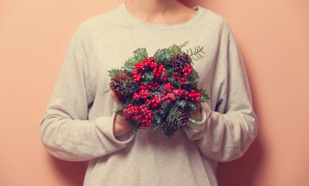 arm bouquet: Female holding a christmas bouquet on pink background