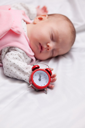 Little baby sleeping in the bed with alarm clock