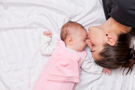 newborn baby mother: Mother and little baby in the bed Stock Photo