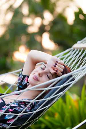 Young redhead woman in a bikini relaxing in a hammock in sunset time Imagens