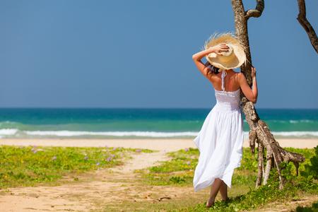 Mujer joven en el sombrero y vestido blanco cerca de la costa. Vista trasera