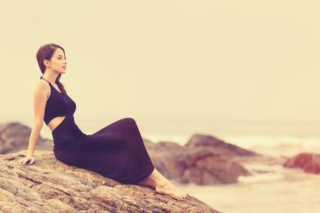 Portriat jeune, femme rousse dans une robe noire près de l'océan
