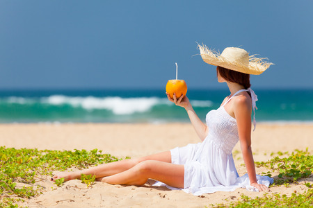 tropical drink: Young woman with coconut cocktail near the sea. Back side view