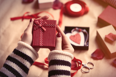 Woman preparing gift for wrapping for Valentine's Day Standard-Bild