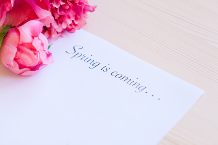 writing paper: Paper with words Spring in coming and flower on the table