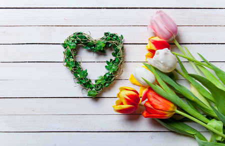 love shape: Beautiful bouquet of tulips and heart shape gift on white wooden background