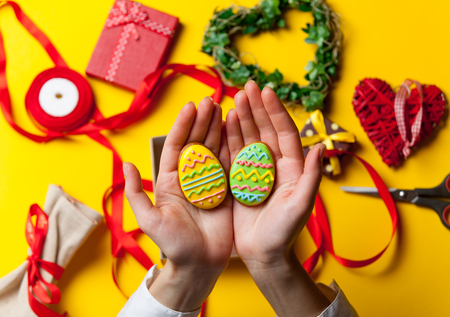 easter cookie: Female hands are holding Easter gingerbread cookie before wrapping