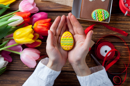 easter cookie: Female hands are holding a Easter cookie egg near flowers before wrapping on violet background