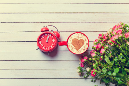 love shape: Beautiful bouquet of roses and cup of cappuccino with retro alarm clock on white wooden background