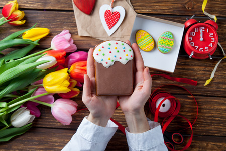 easter cookie: Female hands are holding a Easter cookie near flowers before wrapping on violet background