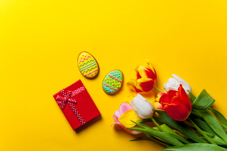 love shape: Beautiful bouquet of tulips and Easter cookies on yellow background