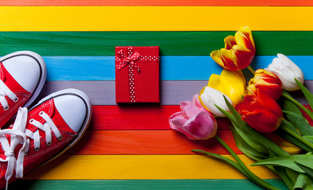 red tulip: bunch of tulips, red gumshoes and gift lying on the wooden colorful table