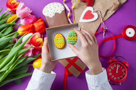 easter cookie: Female hands are holding a gift box with Easter cookie eggs near tulip flowes before wrapping on violet background Stock Photo