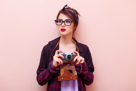 red bandana: portrait of beautiful young woman with camera standing on the pink background
