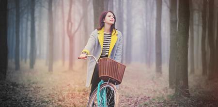 portret van een jonge vrouw met een fiets die zich in het midden van het bos bevindt