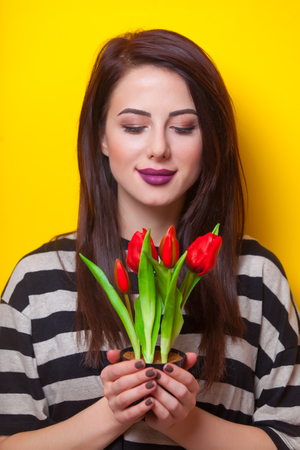 look pleased: portrait of a young beautiful woman with bunch of red tulips standing on the yellow background Stock Photo