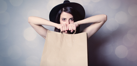 fashion clothing: portrait of the beautiful young woman with shopping bags on the grey background