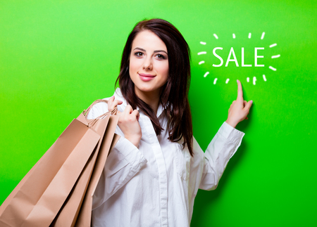 shop tender: portrait of the beautiful young woman with shopping bags on the green background Stock Photo