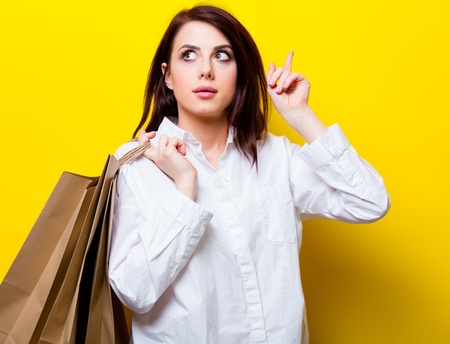 shop tender: portrait of the beautiful young woman with shopping bags on the yellow background