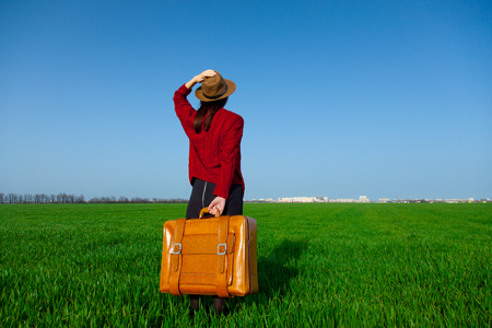 red cardigan: portrait of beautiful young woman with brown suitcase in the field