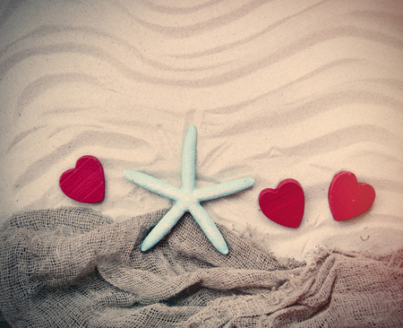 fishnet: blue starfish, red wooden hearts and fishnet lying on the sand Stock Photo
