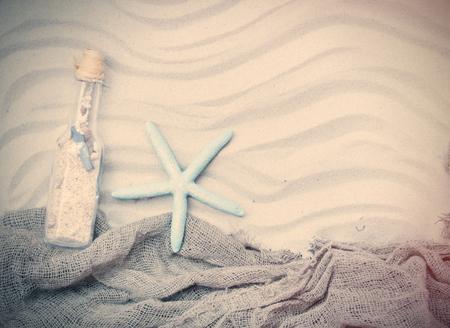 fishnet: blue starfish, souvenir bottle and fishnet lying on the sand