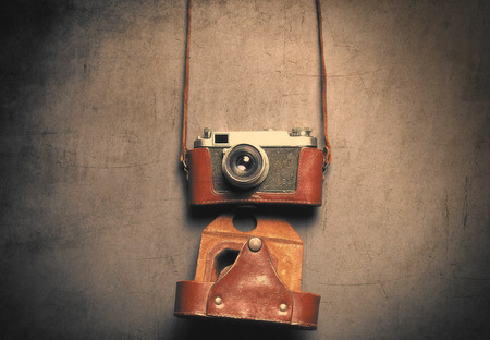 gray backgrund: Retro camera in leather case lying down on grey background