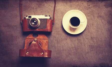 White cup of coffee and retro camera in leather case on grey background