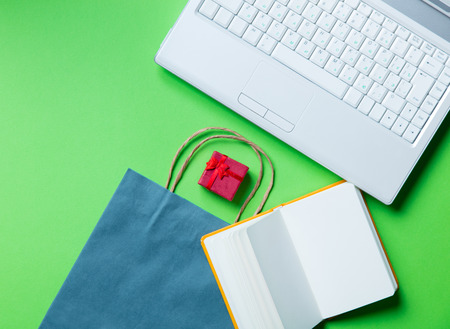 opened bag: gift, opened notebook, blue shopping bag and laptop on the green background