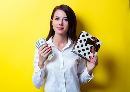 look pleased: portrait of beautiful young woman with gift and money on the yellow background